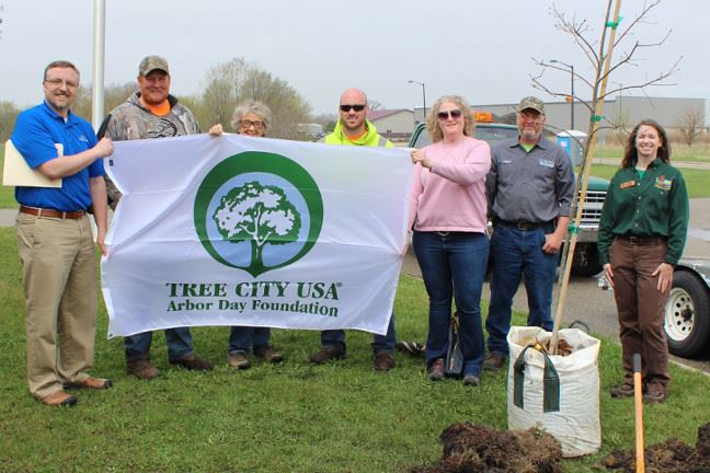 A group of people holding a Tree City USA flag.